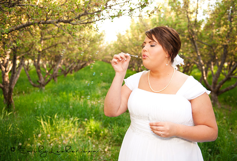 bride blowing bubbles, orchard
