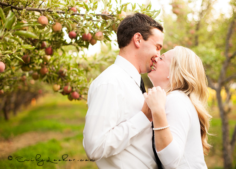 engaged couple laughing in orchard, green orchard