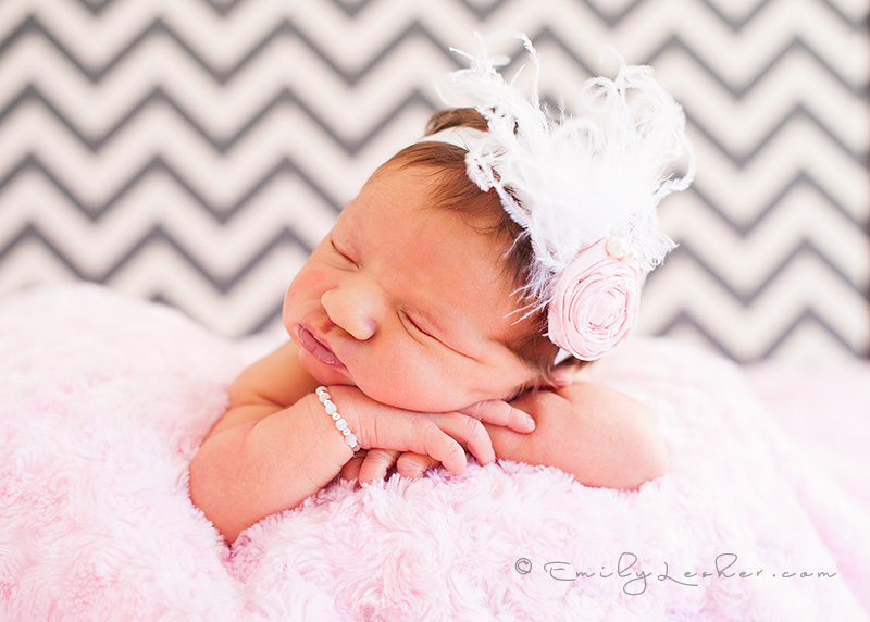baby resting on hands, Cozette Couture pink headband with feathers