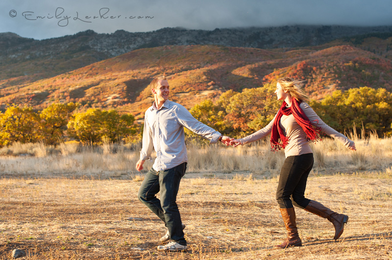 Utah engagement photographer, couple running, mountains, hills, red scarf, moody clouds, dark clouds, meadow, fall leaves, fall colors