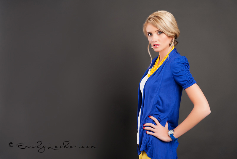 Teresa Peterson modeling for Bella Ella store, yellow bauble necklace, blue cardigan, seamless black backdrop