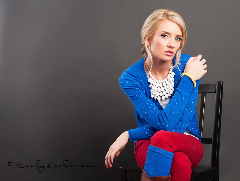 blue cardigan, white necklace, yellow bracelet, blond model. black chair, modeling sitting